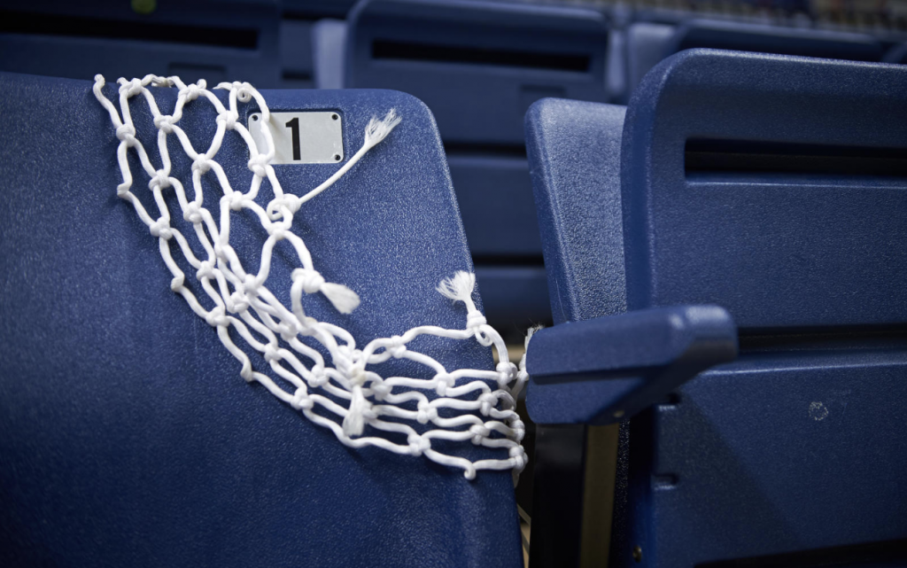 A net cut from a basketball hoop draped over a seat in Gampel Pavilion, as UConn's two basketball teams prepare for the NCAA tournament.