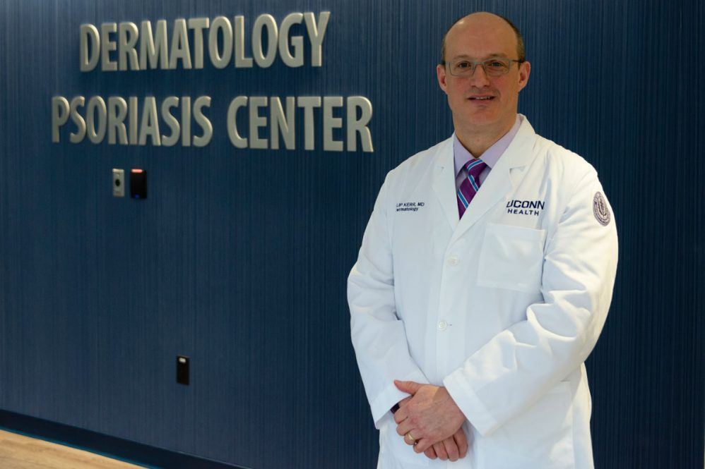 Dr. Philip Kerr in white coat, psoriasis center sign in background