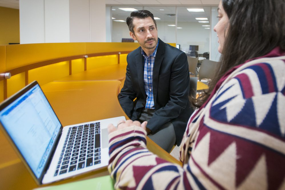 Social work assistant professor Nate Okpych speaks with a student
