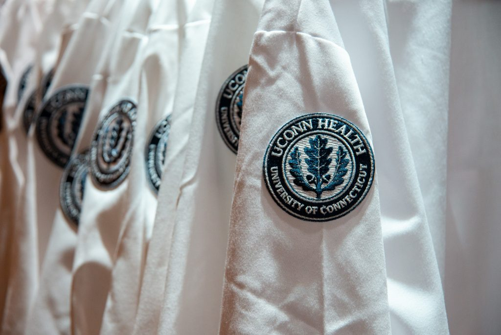 A closeup of the UConn Health logo patch on the shoulder of a white medical coat. Students at UConn Health participating in Match Day 2021 hailed the school's family atmosphere.