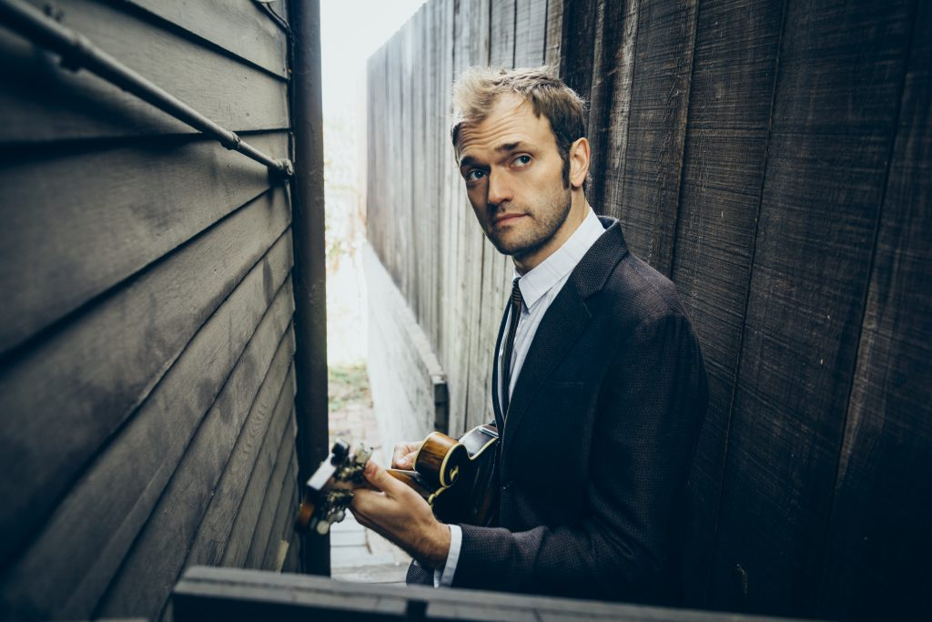 Chris Thile holding a mandolin in a posed photograph. He will perform virtually for a UConn audience on April 17.