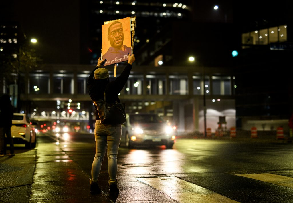 A woman holds up a portrait of George Floyd as people gather outside the Hennepin County Government Center on April 9, 2021 in Minneapolis, Minnesota. People demanding justice for George Floyd gathered tonight outside the Government Center, where the trial of former Minneapolis police officer Derek Chauvin has been ongoing for the past two weeks.