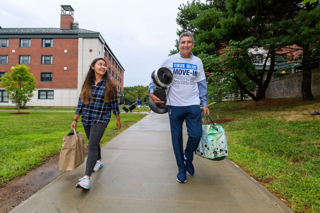President Tom Katsouleas, right, helps Elizabeth Tran '23 (CAHNR) carry her belongings into one of the Towers Residence Halls on Aug. 23, 2019. (Peter Morenus/UConn Photo)