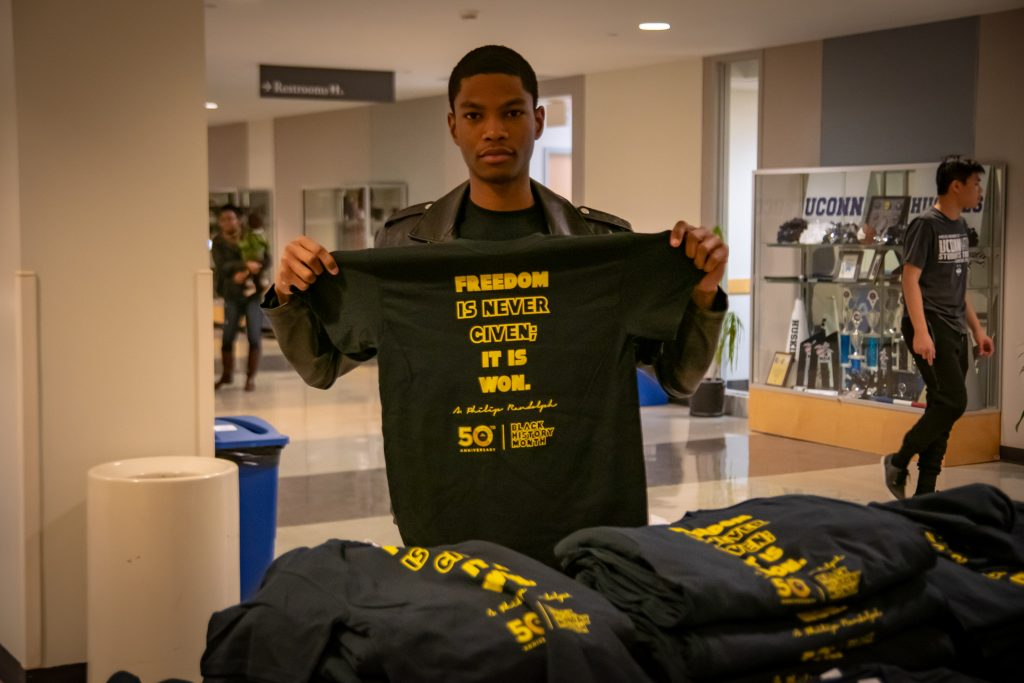Mekhi Amos, a sophomore, holds up a black history month t-shirt outside the Student Union Ballroom on Dec. 7, 2018. (Lucas Voghell/UConn Photo)