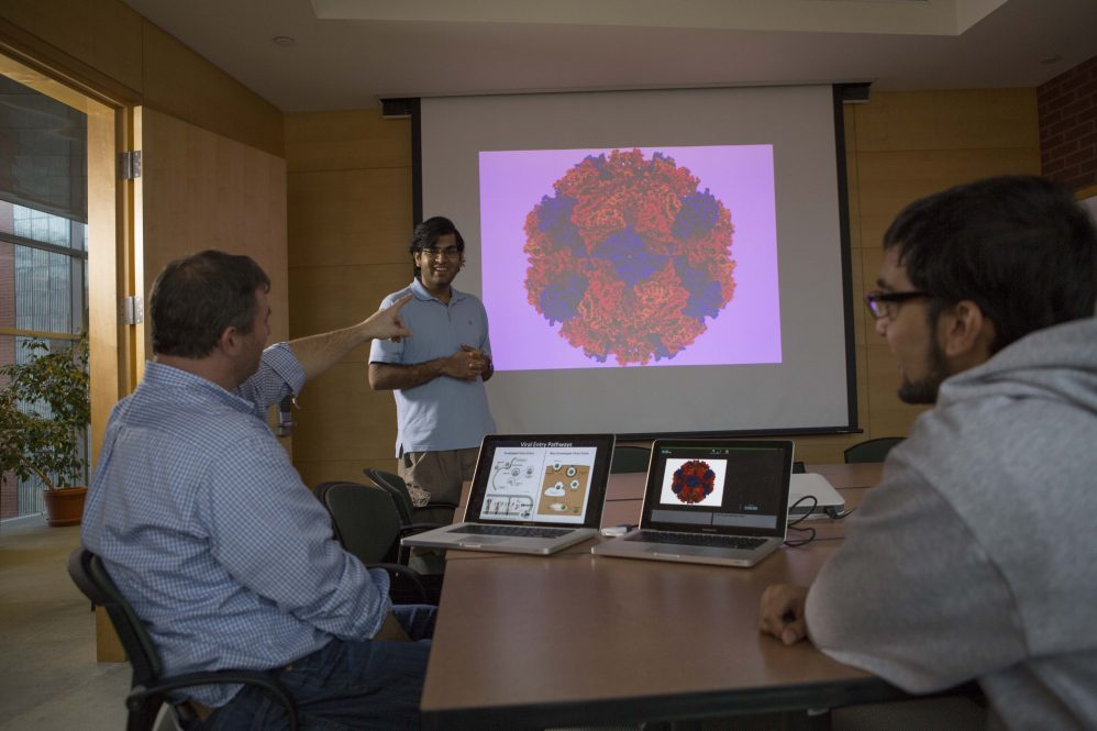 """""""Dr. Eric May (left) discusses virus research with students Prakhar Bansal (standing) and Shaan Kamal (right)."""