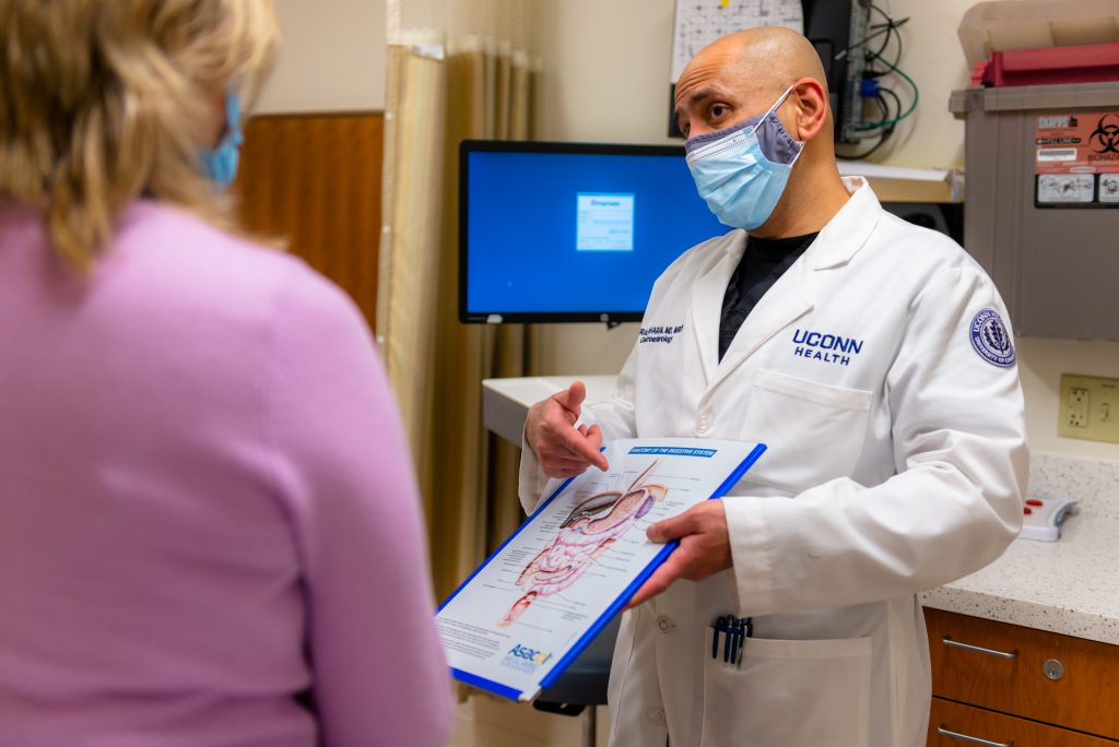 A doctor holding a clipboard with an illustration of the digestive system speaks to a patient in a medical office