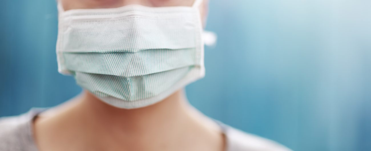 young woman in medical face protection mask indoors on blue background.