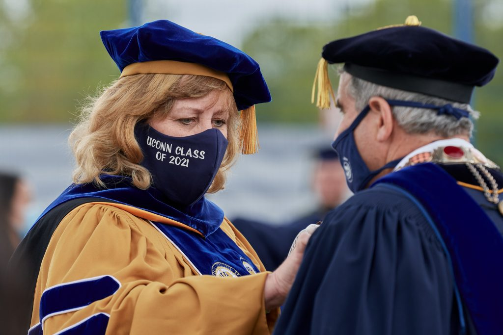 Lucy Gilson, mace bearer, adjusts the necklace for President Thomas Katsouleas before the Commencement ceremony for Doctoral, Pharm. D., Pharmacy B.S., Law, and UConn Health graduates at Pratt & Whitney Stadium at Rentschler Field in East Hartford on May 8, 2021. (Peter Morenus/UConn Photo)