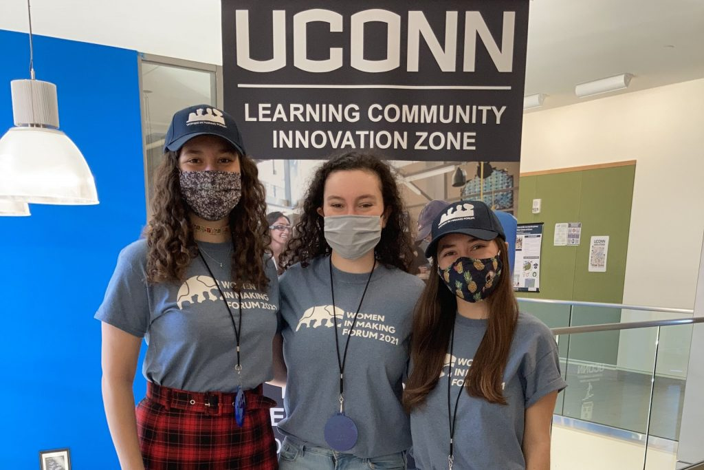 Three female students in masks smiling
