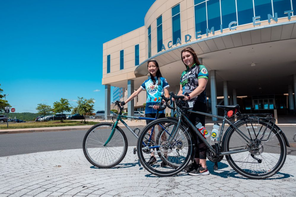 Students with their bikes in front of academic entrance
