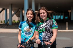 June Chu and Alex Estanislau in their cycling jerseys outside the academic entrance