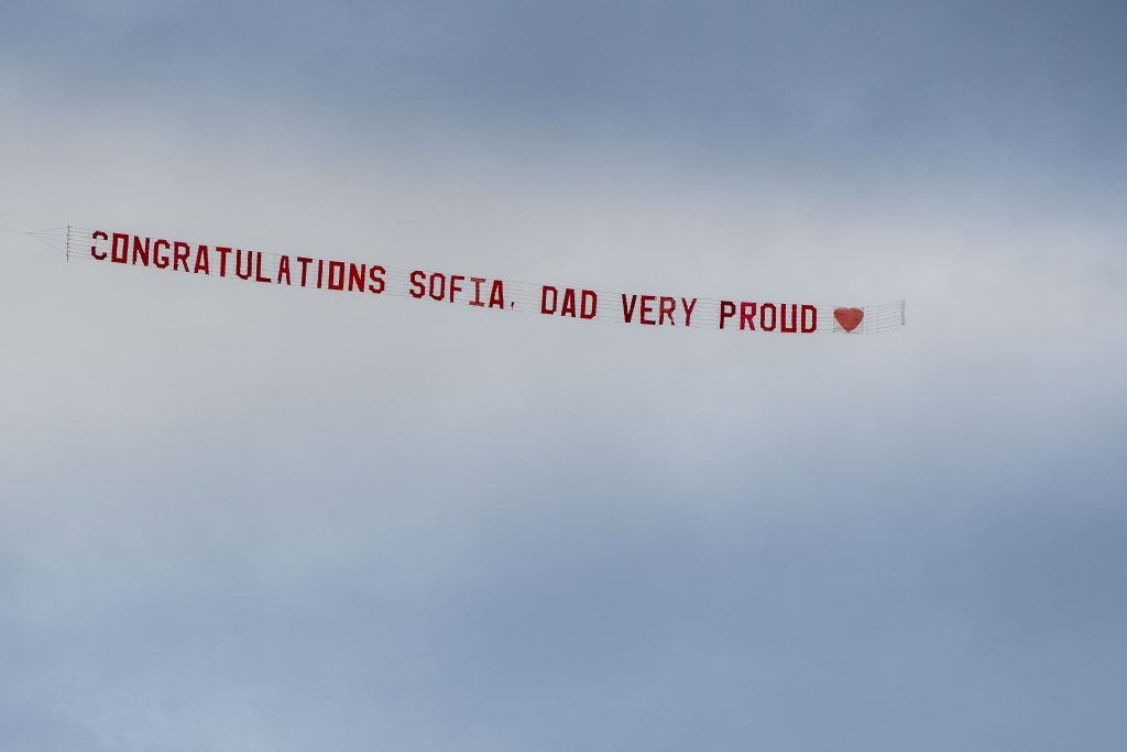 """A banner reading """"Congratulations Sofia. Dad very proud"""" being flown in the sky by an airplane at the 2020 Commencement ceremony at Pratt & Whitney Stadium, Rentschler Field on May 10, 2021. (UConn photo/Sean Flynn)"""