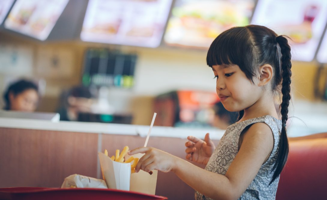 A child in a fast food restaurant. Voluntary policies at fast food restaurants have not increased the likelihood that parents will purchase healthier meals for children, according to new research.