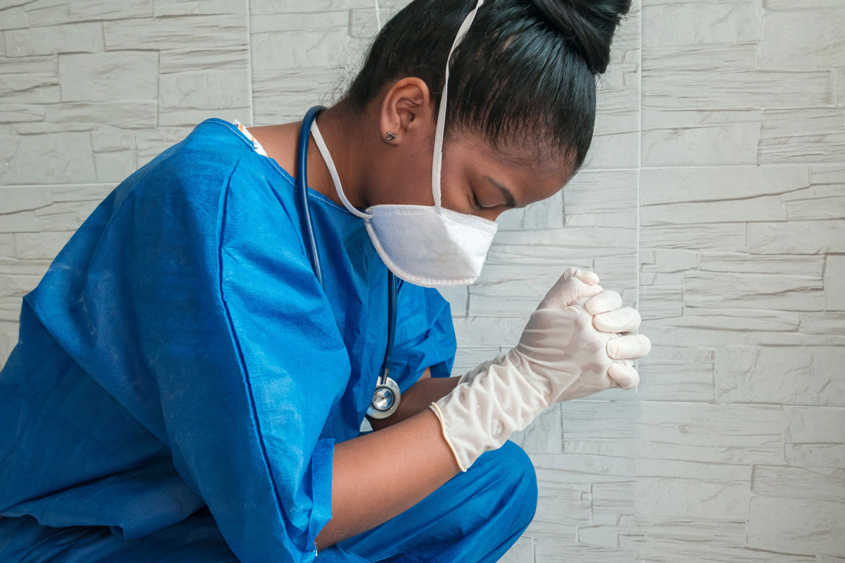 nurse in scrubs with mask and gloves in prayer or reflection