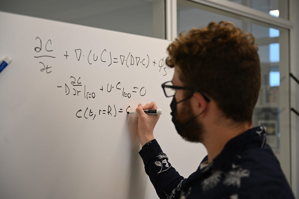 student working on an equation at a whiteboard