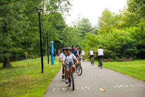 People riding bicycles on a paved trail through a wooded area. Connecticut has more than 2,000 miles of trails.