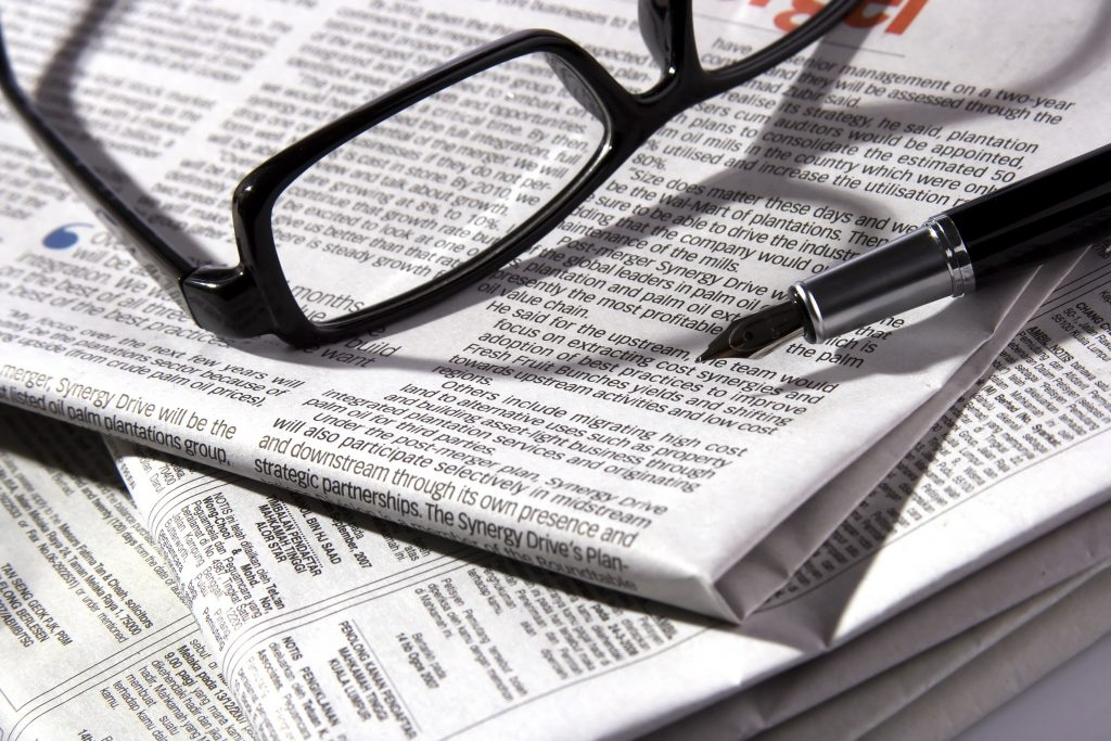 A pair of glasses sitting on a folded newspaper. Social work students who wrote letters to Connecticut newspapers say the experience helped improve their skills as social workers.