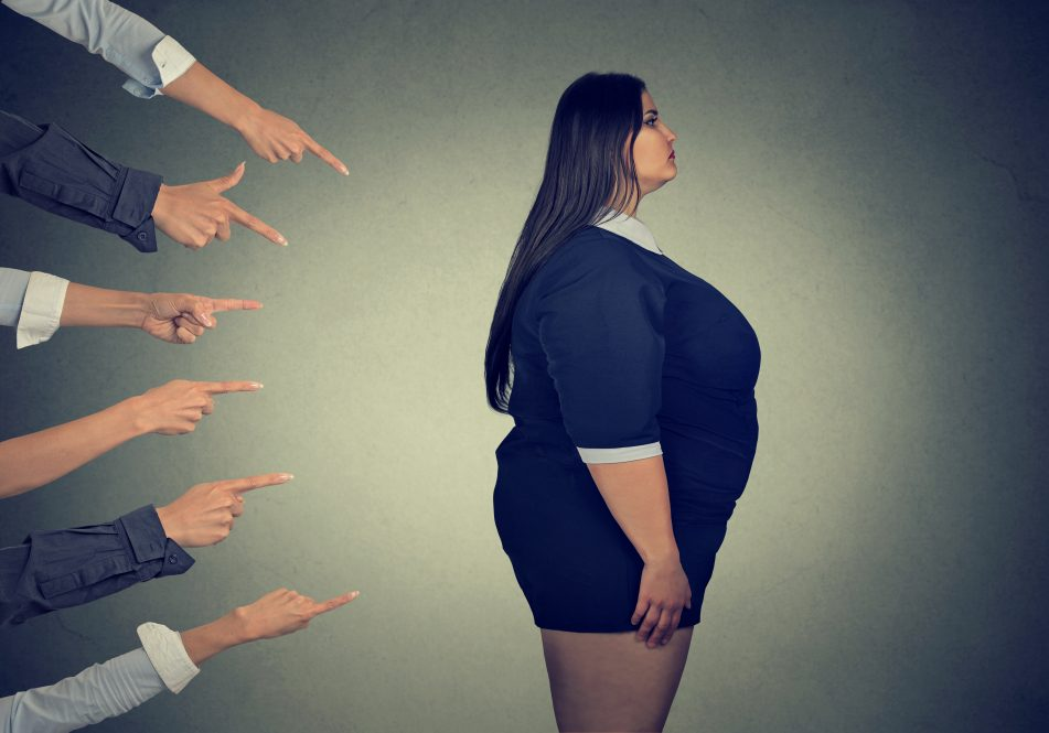 An illustration of hands pointing at a woman who is overweight. A new study examines the experience of weight stigma across six different countries.