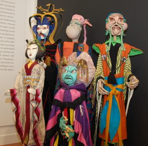"""A display of several rod puppets created by Frank Ballard, UConn's first head of Puppet Arts, for his production of """"The Mikado."""""""
