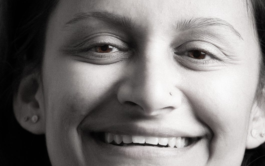 A photograph from the exhibition showing a closeup of a smiling woman's face in black and white.