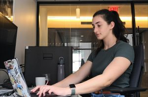 a woman works on a laptop
