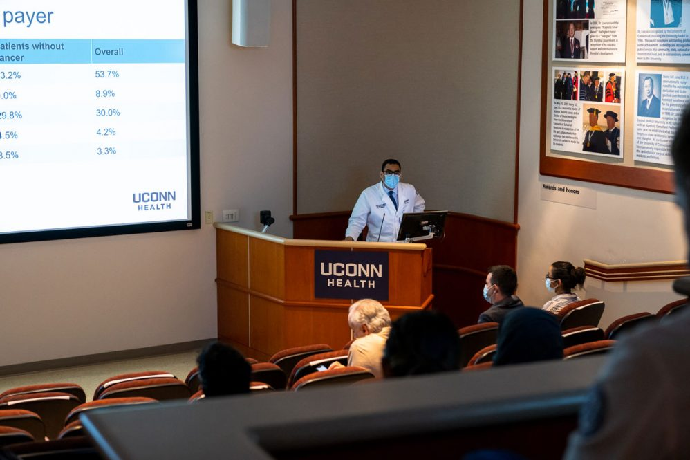Dr. Khalid Shalaby in white coat presenting at podium