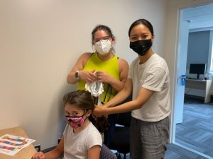 Graduate students Ashley Parker and Yi Wei place an EEG cap on a child..