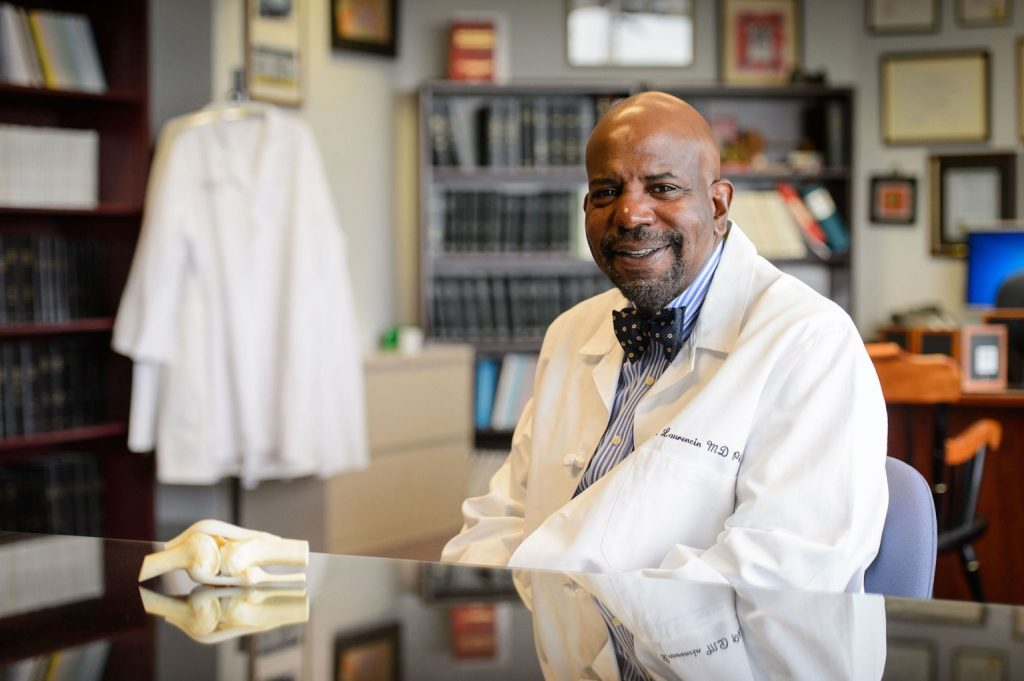 Dr. Cato T. Laurencin in white coat with anatomic model