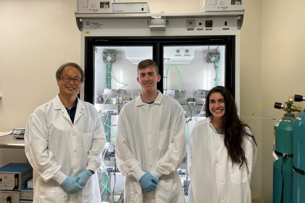 Three scientists stand in front of equipment