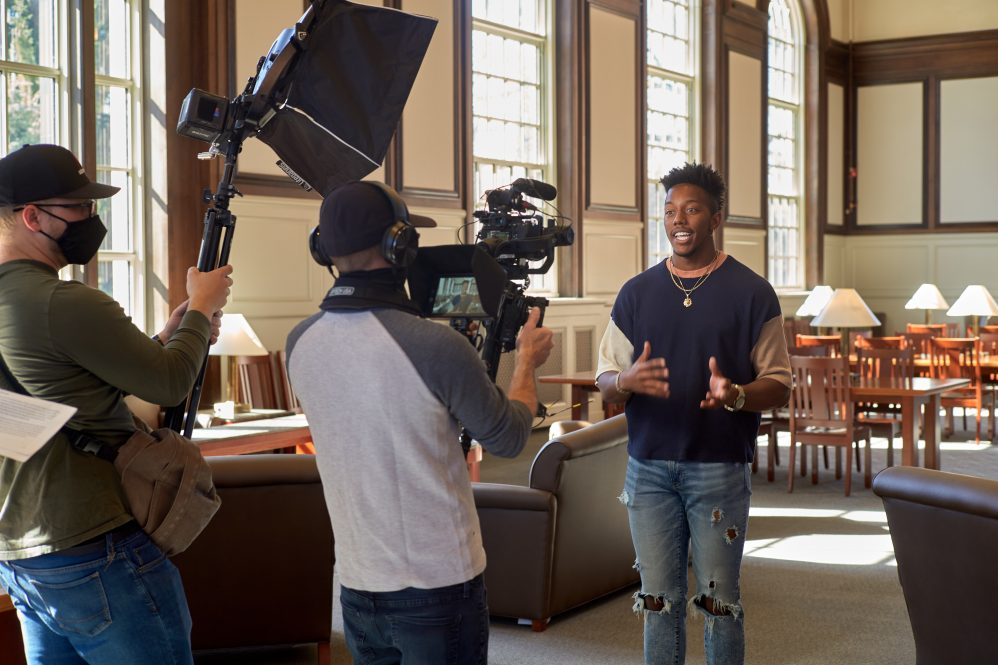 a student being interviewed by a tv crew in the North Reading Room of Wilbur Cross