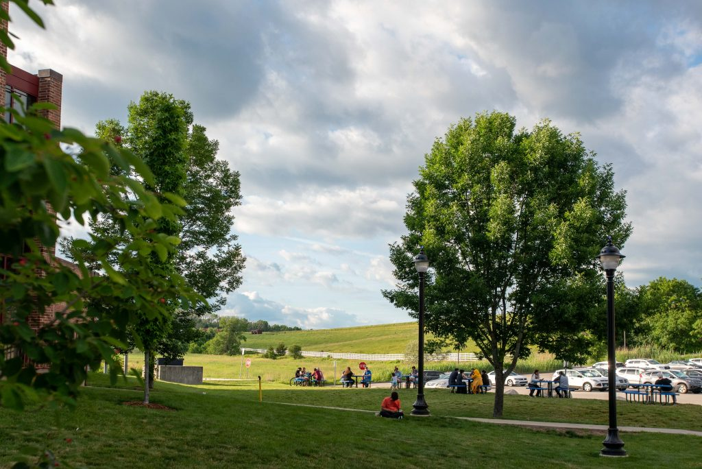 People sitting outside of the UConn Dairy Bar with Horse Barn Hill in the background on June 12, 2021. (Sean Flynn/UConn Photo)