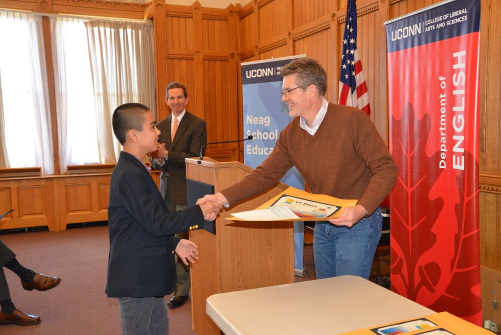Jason Courtmanche presents first place to a middle school student at a 2018 award ceremony for Letters About Litrerature.