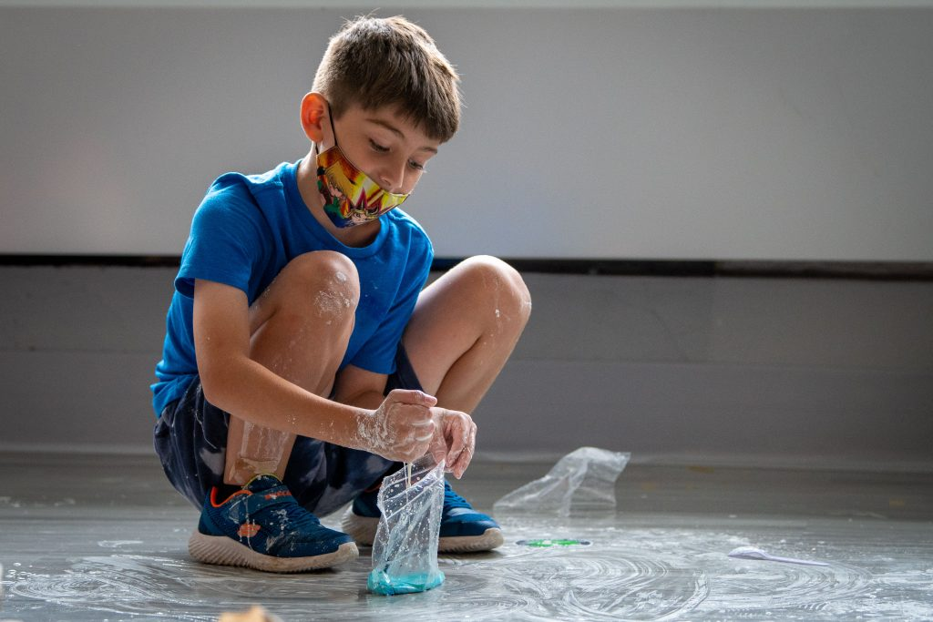 A boy squats to mix water and corn starch with blue food dye to make oobleck.