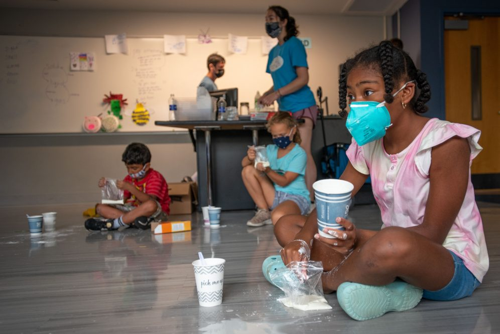 A student at BRAIN Camp, mixes corn starch and water to make oobleck during a camp activity.