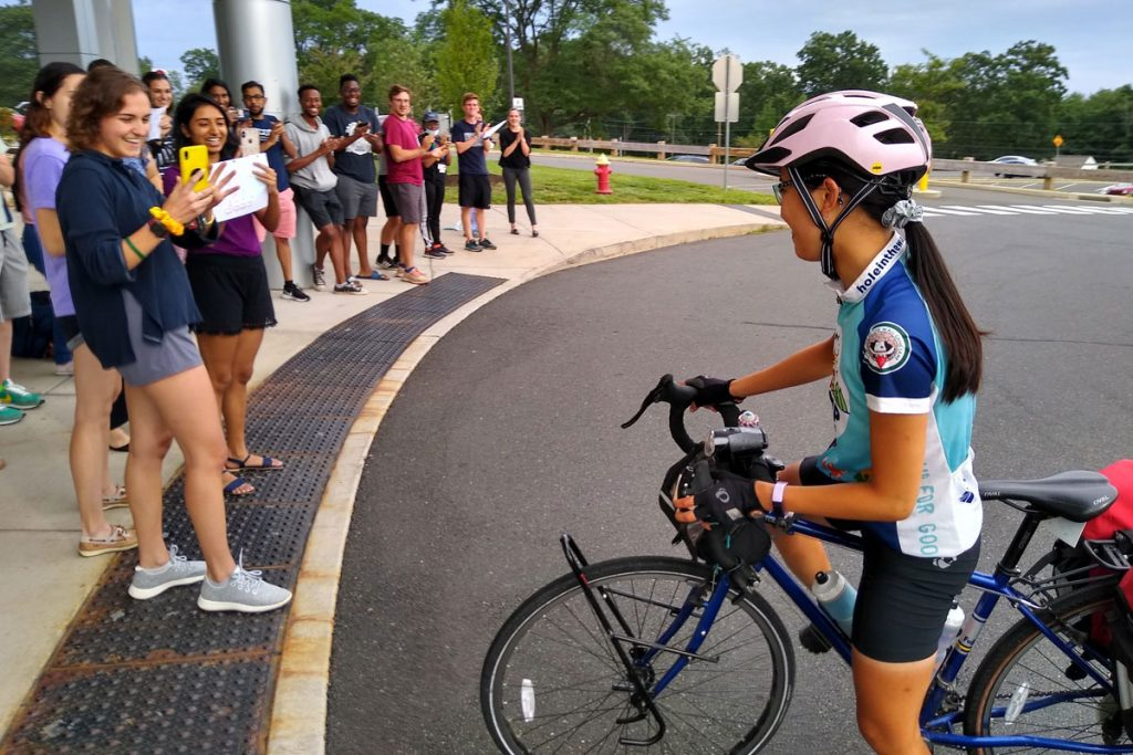Crowd greets June Chu as she arrives on her bicycle at academic entrance