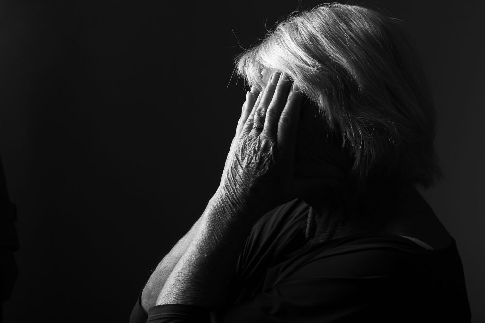 An older woman shields her face with her hands, shrouded in darkness, symbolizing depression. Research shows that ECT given to older adults as psychiatric inpatients is effective at preventing them from dying by suicide in the first months after release from the hospital.