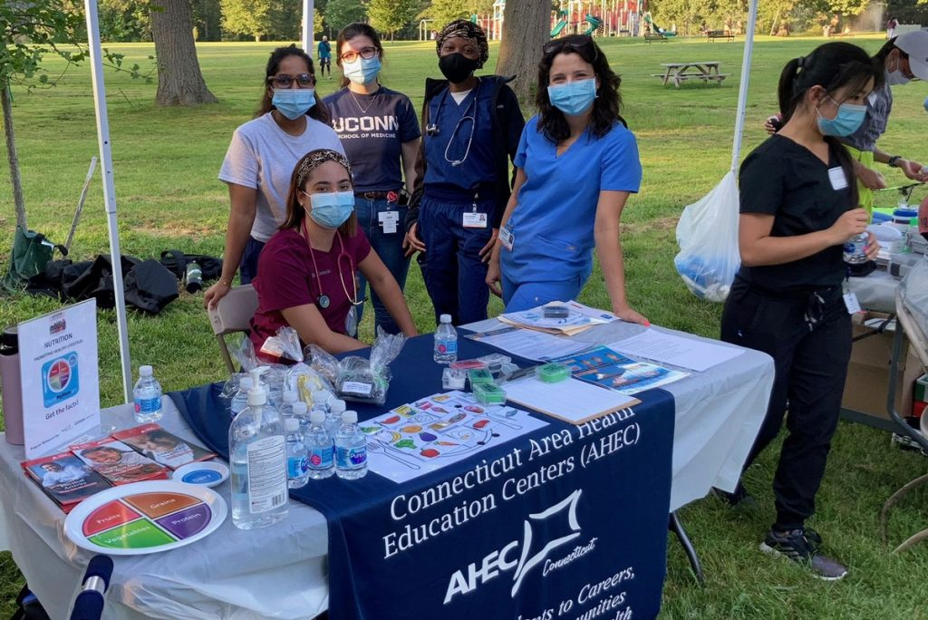 Volunteers at a commnity health clinic, check-in table in a park