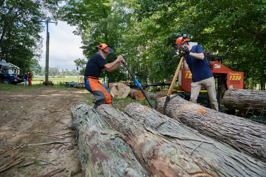 Thomas Worthey, forest sustainability extension educator, left, and Eric Colleran '22 (CAHNR) roll logs into place before using a portable sawmill in the Fenton Tract of the UConn Forest near Horsebarn Hill Road on Aug. 2, 2021. (Peter Morenus/UConn Photo)