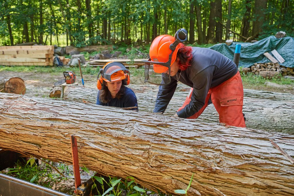 Jose Ayala '22 (CAHNR), left, and Alexandra Pouliot '23 (CAHNR) position a log on a portable sawmill in the Fenton Tract of the UConn Forest near Horsebarn Hill Road on Aug. 2, 2021. (Peter Morenus/UConn Photo)