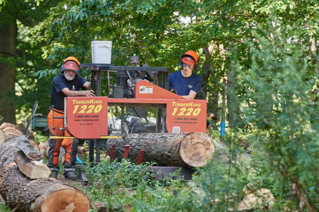 Thomas Worthey, forest sustainability extension educator, left, and Eric Colleran '22 (CAHNR) use a portable sawmill to cut boards from a log in the Fenton Tract of the UConn Forest near Horsebarn Hill Road on Aug. 2, 2021. (Peter Morenus/UConn Photo)