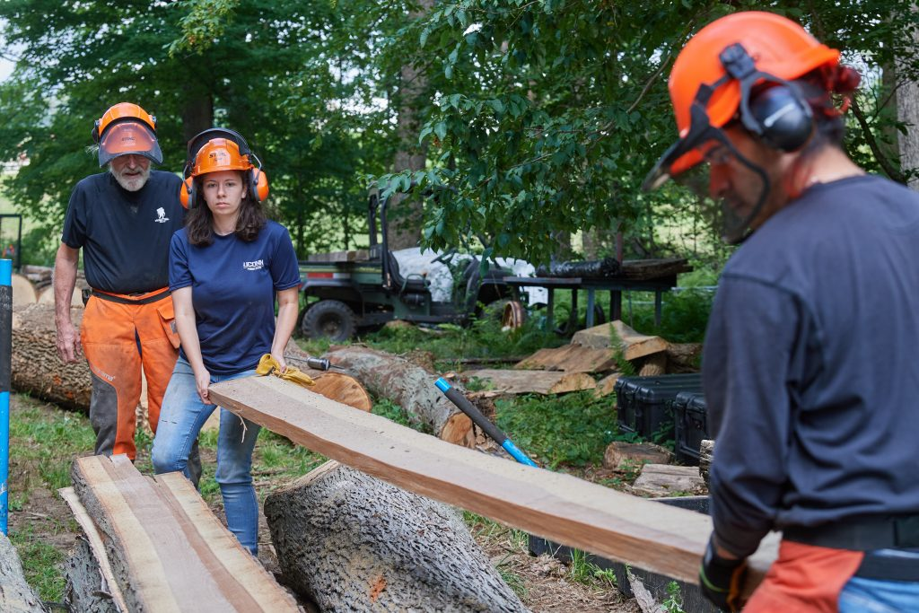 Alexandra Pouliot '23 (CAHNR), center, and Jose Ayala '22 (CAHNR), right, lift a newly cut board from a log as Thomas Worthey, forest sustainability extension educator, looks on in the Fenton Tract of the UConn Forest near Horsebarn Hill Road on Aug. 2, 2021. (Peter Morenus/UConn Photo)
