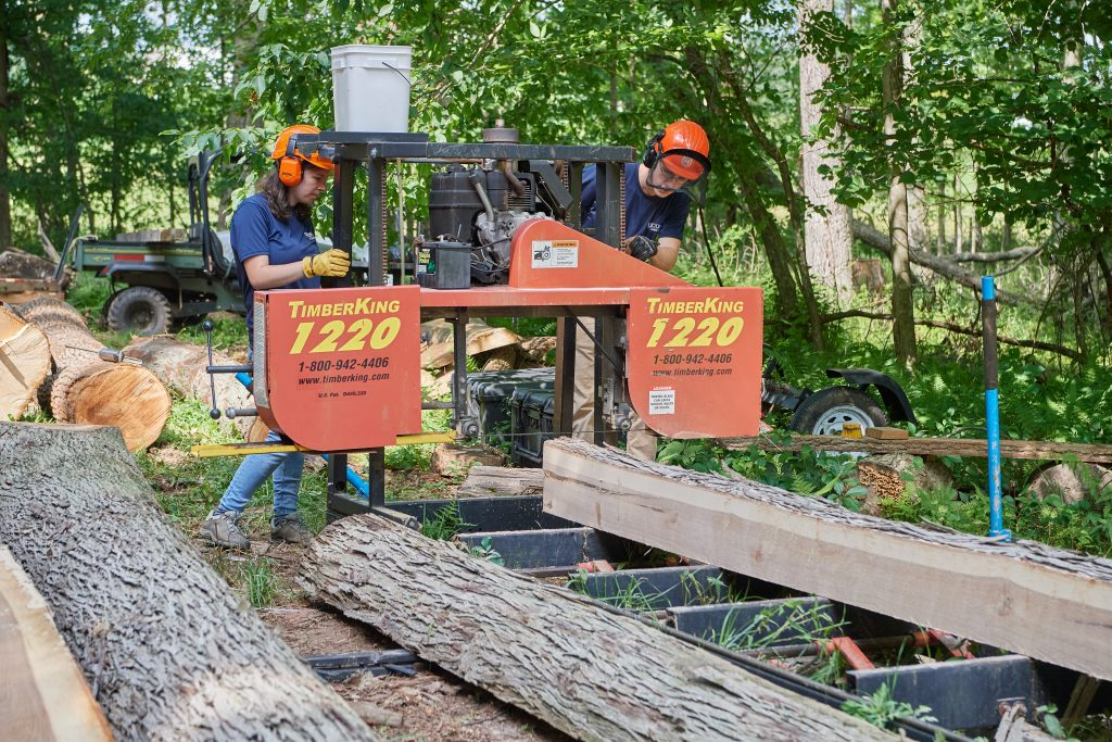 Alexandra Pouliot '23 (CAHNR), left, and Eric Colleran '22 (CAHNR) use a portable sawmill in the Fenton Tract of the UConn Forest near Horsebarn Hill Road on Aug. 2, 2021. (Peter Morenus/UConn Photo)