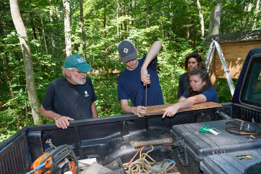 Thomas Worthey, forest sustainability extension educator, left, Eric Colleran '22 (CAHNR), Jose Ayala '22 (CAHNR)and Alexandra Pouliot '23 (CAHNR) erect a new sign for the Moss tract of the UConn Forest on Aug. 2, 2021. (Peter Morenus/UConn Photo)
