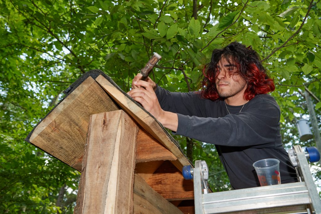 Jose Ayala '22 (CAHNR) nails down shingles on a new sign for the Moss tract of the UConn Forest on Aug. 2, 2021. (Peter Morenus/UConn Photo)