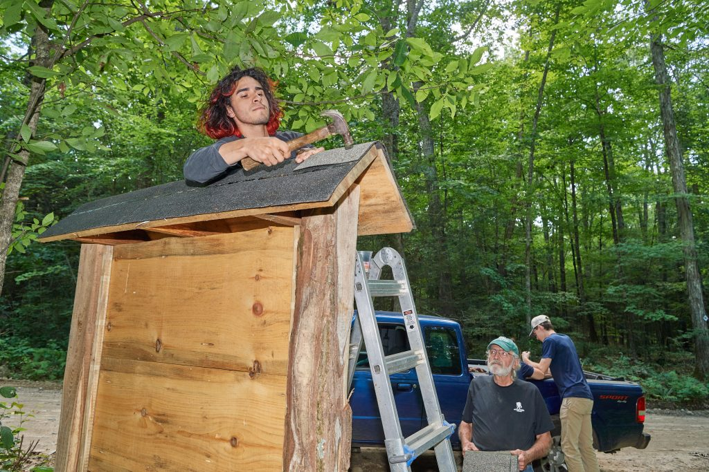 Jose Ayala '22 (CAHNR), left,  nails down shingles on a new sign for the Moss tract of the UConn Forest on Aug. 2, 2021. (Peter Morenus/UConn Photo)