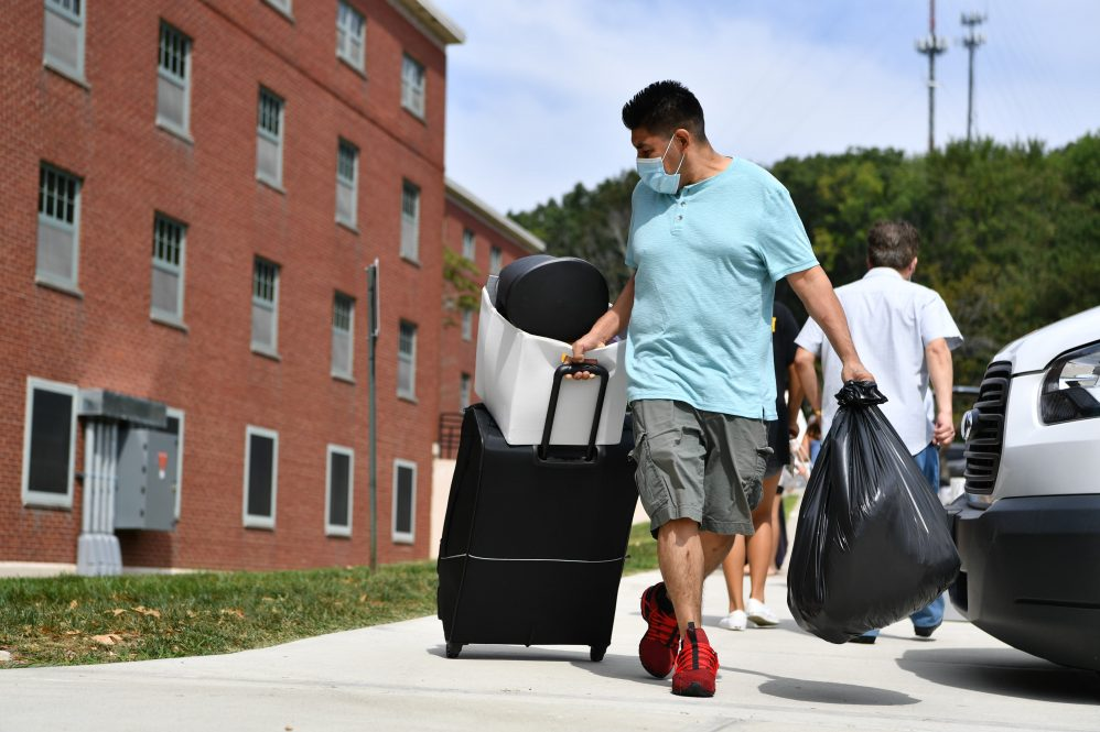 A student with a facemask carrying a suitcase behind him outside a residence hall, preparing to move in.