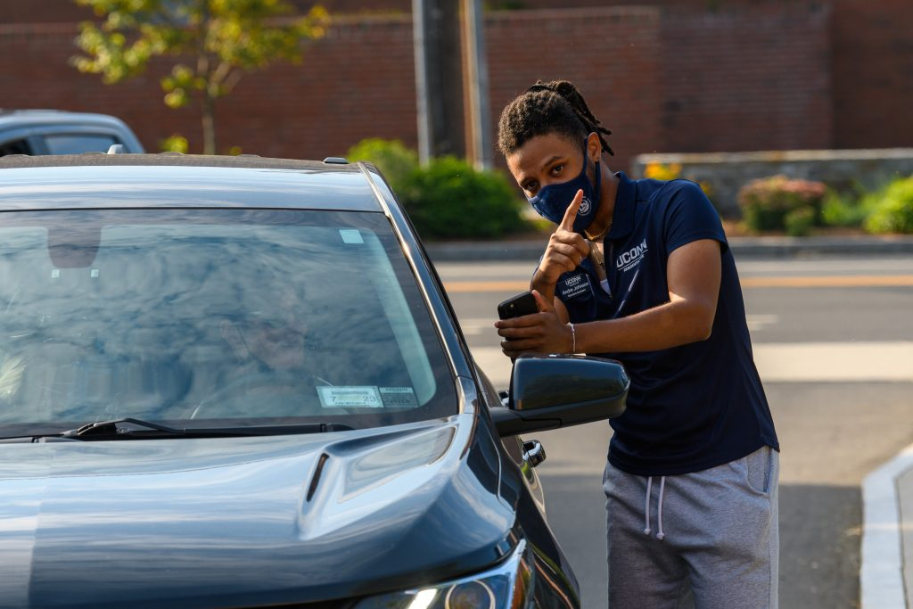 Andre Johnson '23 (CLAS), a residence assistant, gives directions for students tp move into dorms at the North Campus Residence Halls on Aug. 27, 2021. (Peter Morenus/UConn Photo)