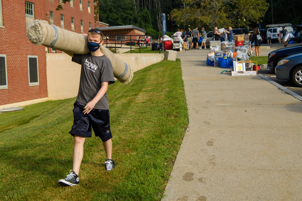Alexander Lee '25 (ENG) carries a rug into his  North Campus Residence Hall dorm on Aug. 27, 2021. (Peter Morenus/UConn Photo)