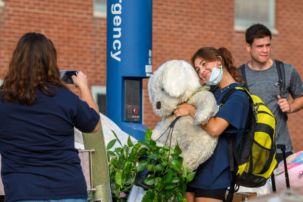 Bella Funk '25 (CLAS) poses for a photo while holding a teddy bear outside a North Campus Residence Hall before carrying her belongings indoors on Aug. 27, 2021. (Peter Morenus/UConn Photo)