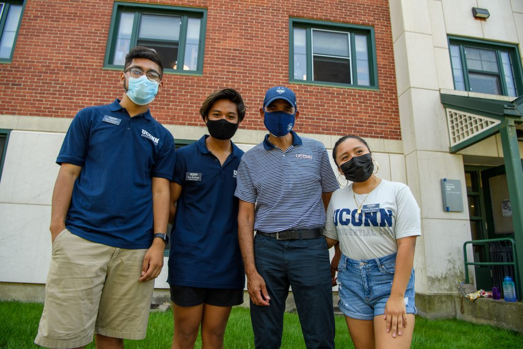 Andrew Agwunobi, interim president, third from left, poses for a photo with residence assistants Taqi Rahman, left, Troy Barbieto, and Marcielo Fabian outside the Towers Residence Halls on Aug. 27, 2021. (Peter Morenus/UConn Photo)